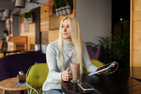 Young blond Woman using Tablet and Drinking Coffee. Relaxing in Cozy cafe, Sit on the Chair and listening with pleasure in headphones an audio book or music