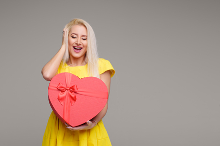 Blond girl in yellow dress with heart shape box for Valentine Day Holiday on grey background. Copy space for text Reklamní fotografie