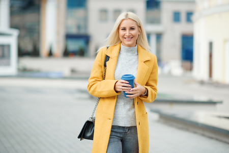 Young blond woman in a yellow bright coat with a cup of coffee to go, hurries to meet on a city street Reklamní fotografie - 116001286