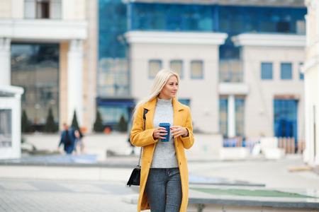 Young blond woman in a yellow bright coat with a cup of coffee to go, hurries to meet on a city street Reklamní fotografie - 116001296