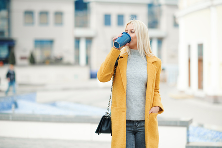Young blond woman in a yellow bright coat with a cup of coffee to go, hurries to meet on a city street Reklamní fotografie - 116001300