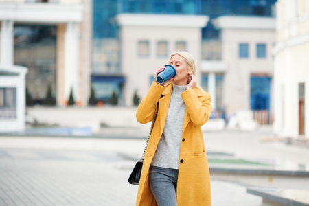 Young blond woman in a yellow bright coat with a cup of coffee to go, hurries to meet on a city street Reklamní fotografie - 116001299