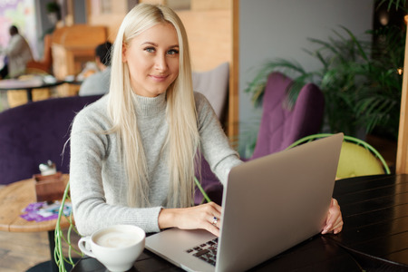 Confident young woman in casual wear working on laptop while sitting in creative office or cafe and woking. Holding a cup of coffee and smiling Reklamní fotografie