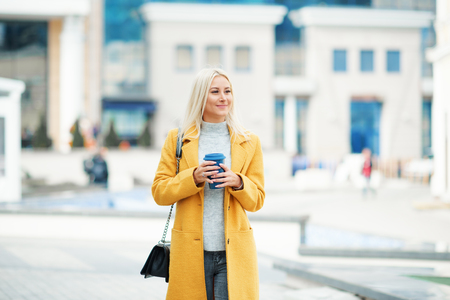 Young blond woman in a yellow bright coat with a cup of coffee to go, hurries to meet on a city street Reklamní fotografie - 116001383