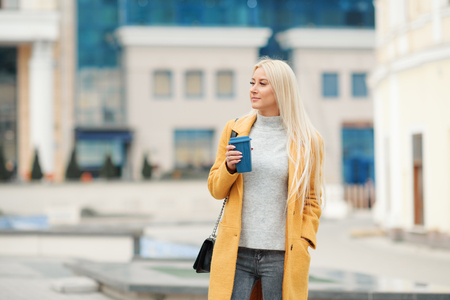Young blond woman in a yellow bright coat with a cup of coffee to go, hurries to meet on a city street Reklamní fotografie - 116001380