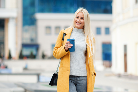 Young blond woman in a yellow bright coat with a cup of coffee to go, hurries to meet on a city street Reklamní fotografie