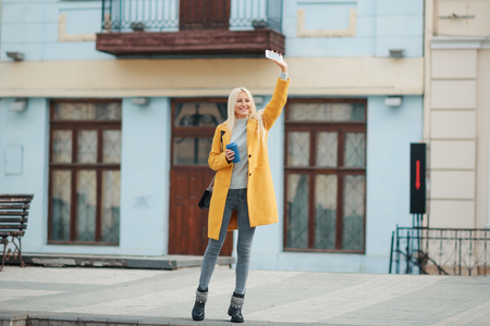 A young blond woman in a yellow bright coat is standing in the middle of the street and talking on the phone. Waiting for a meeting of friends. Holds a cup of coffee to go.