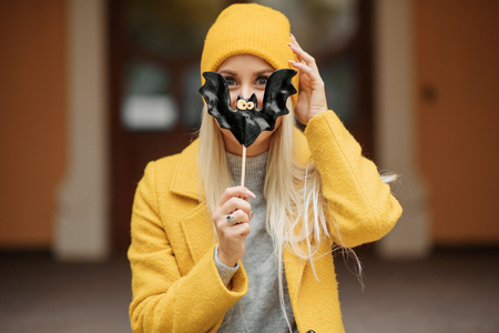 Fashion portrait pretty cool girl in yellow coat and hat with lollipop black bat having fun in autumn city