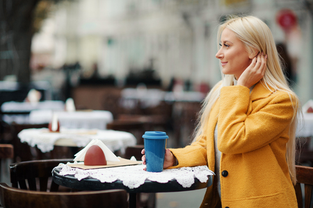 Coffee togo. A young blond woman in a yellow bright coat sits in a street cafe at a table with a glass of coffee. Talking on the phone and waiting for a date of friends or a guy