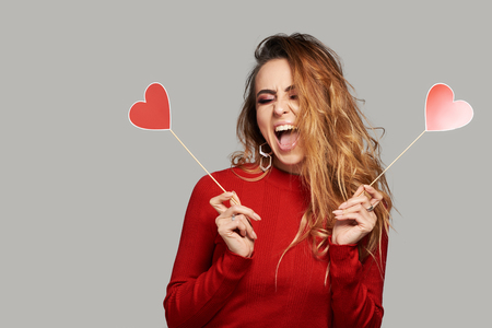 Valentines Day. Surprised redhair woman with hearts in her hands. Young woman with red hearts on grey background. studio shot with hearts with space for text Reklamní fotografie
