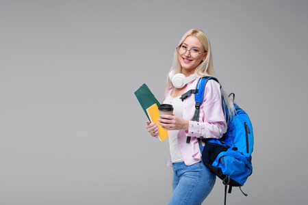 Young female student in headphones with backpack drinking coffee, smiling. Startup, freelancer. Learning foreign languages online, exam preparation