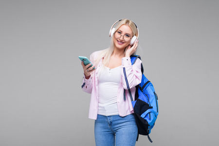 Smart young blond woman in headphones satisfied with learning language during online courses using smartphone, smiling female student doing homework task, searching information via mobile phone