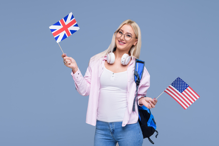 Education, foreign language translator, english, student - smiling blond woman in headphones holding American and British flags. Distance learning