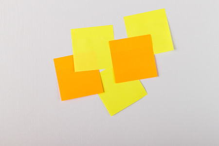 yellow and orange sticky notes on a white wall.