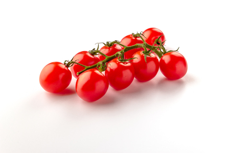 Small cherry tomato on white background. Close-up.