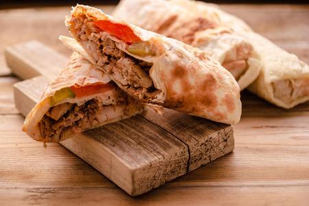 Doner Kebab Gyros Shawarma beef roll in pitta bread Wrap sandwich on wooden background.