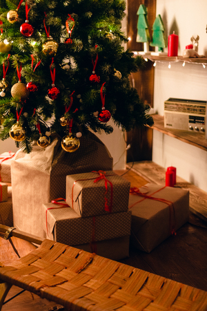 gift boxes under the Christmas tree. Colorful brown, golden Gift boxes with ribbon bow present on holiday.