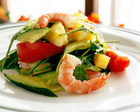 Spring creative fresh salad of shrimp, avocado, tomato, potato, cucumber. Sunlight from the window. Dish on a white plate. Close-up.