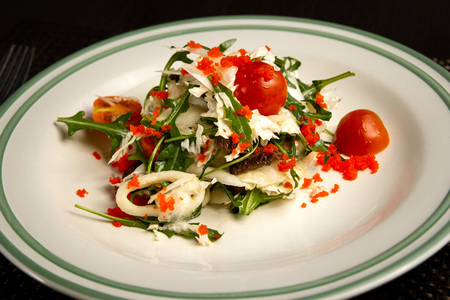 Seafood salad. Salad with shrimps, mussels, squids, lettuce, arugula, spinach and other greens on a white plate on a dark wooden background, decorated with fresh vegetables. close up.