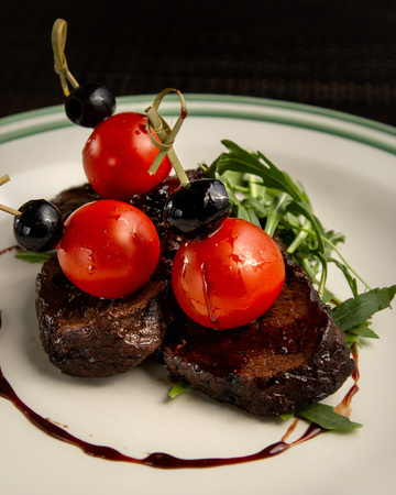 Beef medallions with cherry tomatoes in a white plate on a dark background