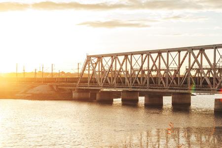 Sunset above railway bridge over water reservoir.