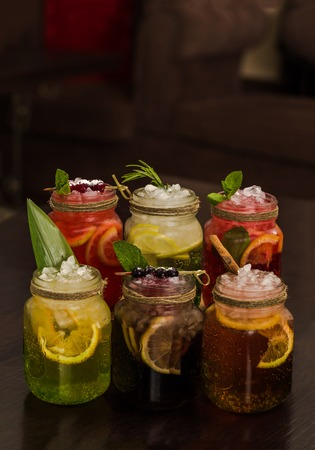 Six glasses of homemade different decorated summer drinks of lemonades on a wooden table. Copy space