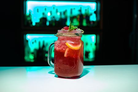Red homemade lemonade on a bar with blue backlighting Copy space on bar blurred background