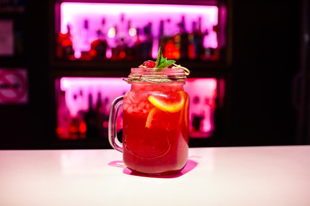 Red homemade lemonade on a bar with pink backlighting Copy space on bar blurred background.