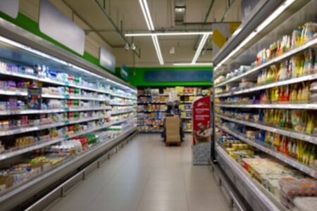Blurred image of dairy products and sauces in store. Wide perspective view of empty store aisle and shelves, defocused blurry background with bokeh light in store. Business concept