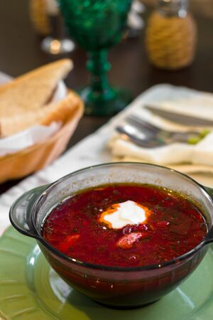 Russian ukrainian soup borscht with greens and sour cream. Beetroot soup in bowl on white wooden table.