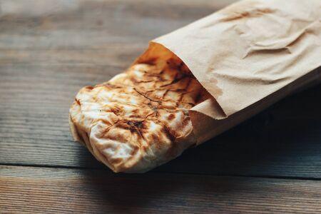 Doner Kebab Gyros Shawarma beef roll in pitta bread Wrap sandwich on wooden background. copy space.