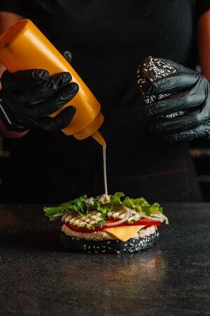 Koch auf dem Küchentisch, der die Zutaten des Burgers ausmacht.