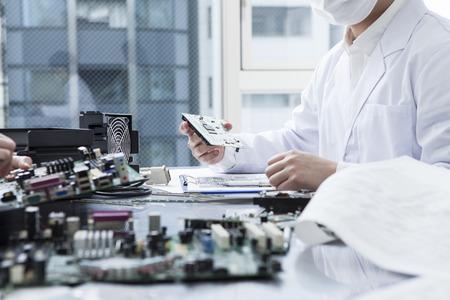 Homme d'examiner le circuit électronique