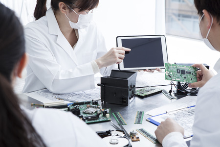 describes: Women describes electronic circuits tablet Stock Photo