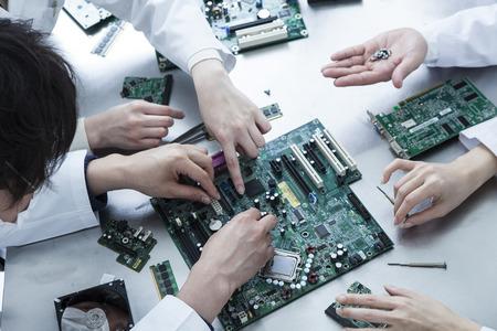 男性と女性が白衣を着て電子回路を調査するには