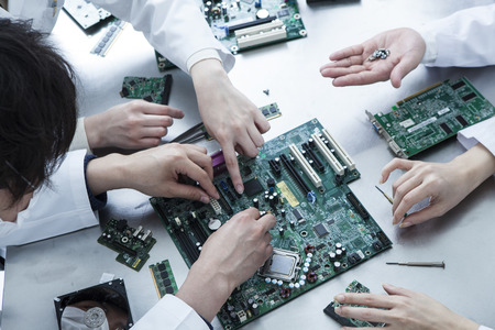 Men and women wearing a white coat to investigate the electronic circuit
