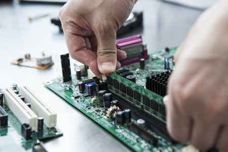 motherboard: Close-up of the hands of the man wearing a white coat Stock Photo