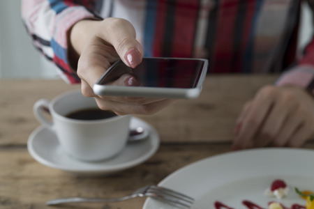 grabbing hand: Woman to use a smart phone while eating a cake Stock Photo