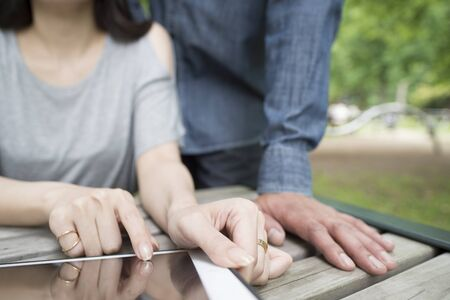 new world order: Couples View tablet together in the park Stock Photo