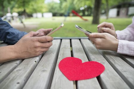 new world order: Man and Women who use the smart phone in the park Stock Photo