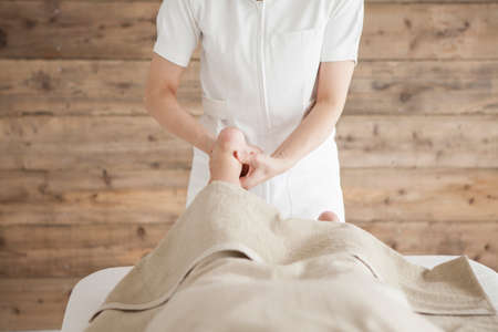 power suppliers: Woman to be massaging the ankle with both hands