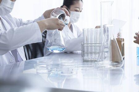 Trois chimistes à l'étude du liquide bleu Banque d'images