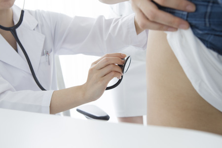 doctor examine: Young female doctor examine male patient with stethoscope