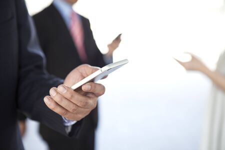 phone business: A group of business people looking at a cell phone and laughing