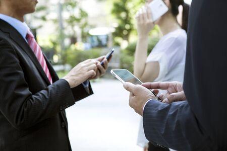 using phone: Closeup of three people using smart phone.