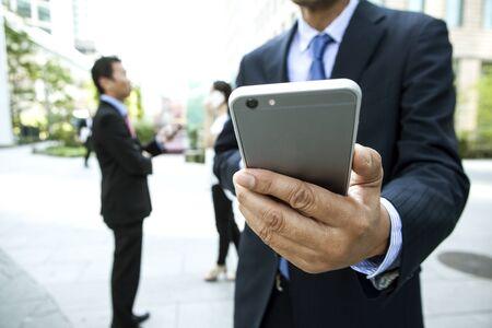 many people: Closeup of three people using smart phone.