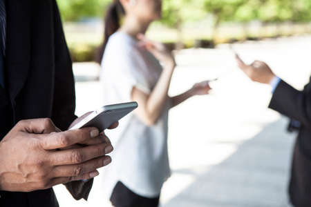 mucha gente: Primer plano de tres personas que usan teléfonos inteligentes.