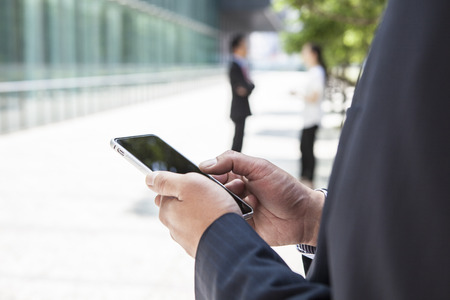 gratified: Happy businesspeople using mobile phones