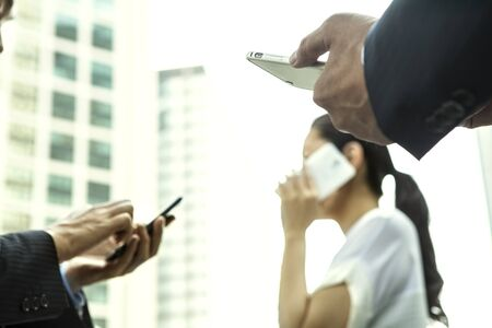 gratified: Happy businesspeople using mobile phones at office lobby - plenty of copyspace. Stock Photo