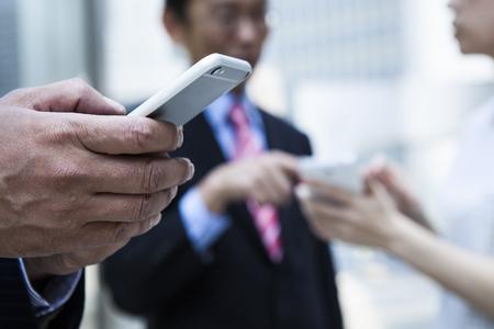 同僚とのスケジュールをチェックします。会議室の窓に立っている間携帯電話の画面を見て正式な摩耗のビジネス人々 のグループ 写真素材